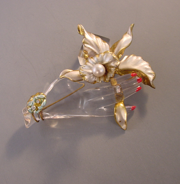 LUCITE jelly belly trembler brooch, a hand holding an orchid