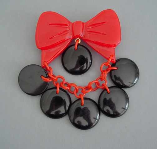 SHULTZ bakelite red bow brooch with black disks