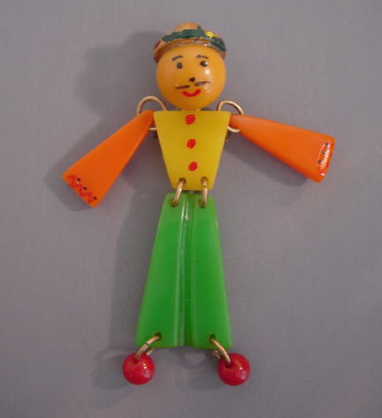 SHULTZ bakelite jointed man brooch, green, yellow and orange