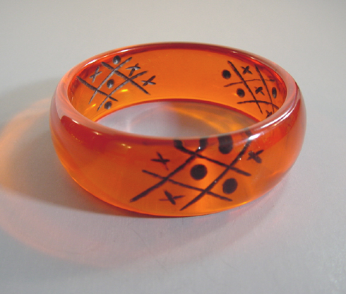 SHULTZ bakelite orange transparent bangle with reverse carved and painted dark blue
