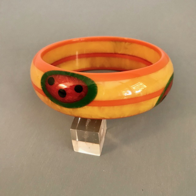 SHULTZ bakelite watermelon motif bangle with 5 rows of laminated marbled yellow and orange