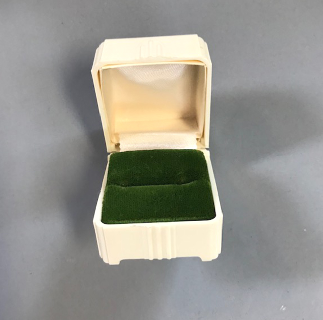 DECO style white plastic ring box that opens to green velvet ring slot