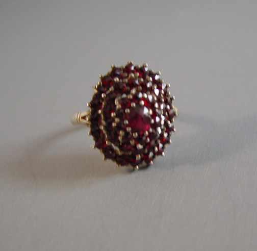 BOHEMIAN garnet and gilt sterling domed oval ring with four tiers