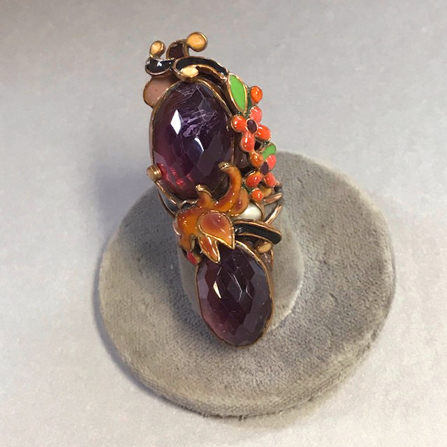 VEGA MADDUX ring with two high domed purple faceted stones surrounded with green, orange, orange and black enameled flowers and scrolls